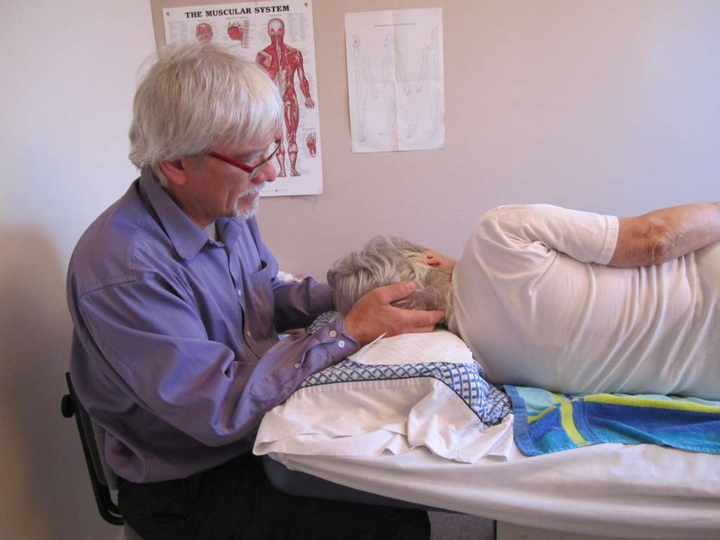 Photo of Fred in a purple shirt sitting with hands on the head of a patient. Patient in white t-shirt is laying down on massage table, facing away from camera. Massage table has a pillowcase with a sheet of paper towel on top as well as a blue and yellow printed towel on the white lined bed. Anatomy photo of the muscular system visible behind Fred's head.