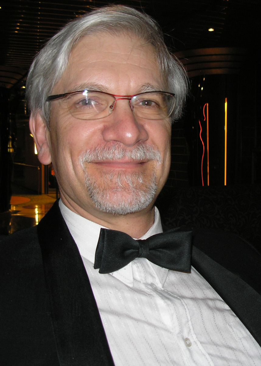 Fred Samorodin in a Tux, smiling at camera in front of dark background.